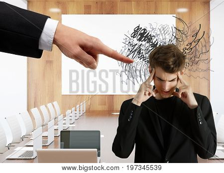 Hand pointing at pensive businessman with scribble. Meeting room background. Stress concept