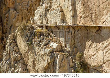 Yellow stone wall with rusty clamps El Camino del Rey Malaga Spain