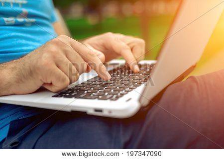 Close-up shot of handsome man's hands touching laptop computer's screen. Businessman using a laptop computer and sitting on a bench.. Sun flare