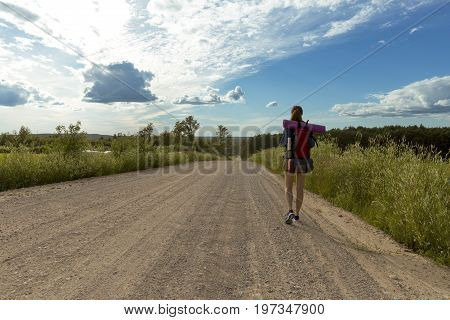 Young woman with backpack hiking in the countryside. Stress free travel concept.