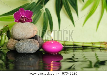 Pebbles laid  on the left out in zen lifestyle with an orchid at the top and a pink candle lit