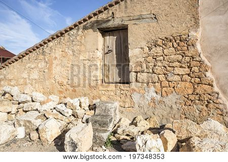 a rustic country house made of stones with a wooden door