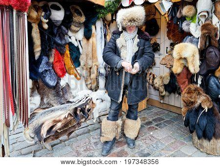 Riga Latvia - December 24 2015: Male seller of fur items on Christmas market in Riga Latvia