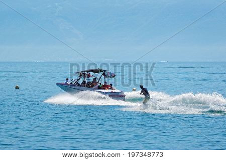 Motorboat With People Aboard And Man Wakesurfing In Lake Geneva