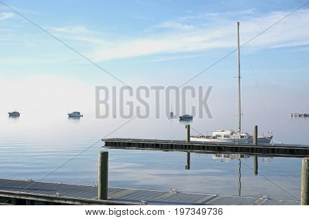 Sail boat on calm water with blue sky with some clouds and white fog
