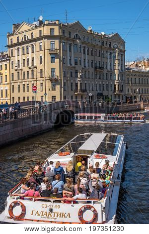 Saint Petersburg, Russia - June 17, 2017: Tourist boat moves along the Moika river. Nearby is the Hermitage. It is a popular trip in the city