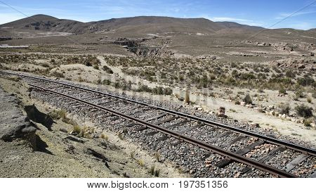 A railway track leading through the dry landscape near Sumbay, southern Peru