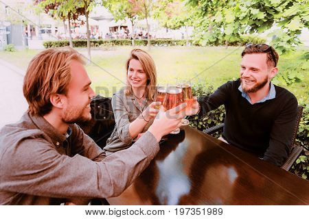 Smiling Young Friends Clanging Glasses Of Beer