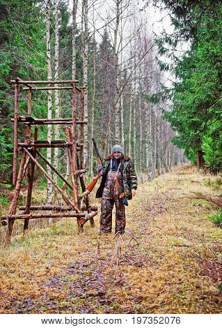 Male hunter at watchtower in autumn forest in Latvia Baltic country