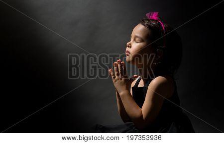 Little girl praying isolated over black background
