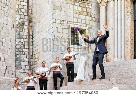 Bride And Groom And Musicians Near Church In Dubrovnik
