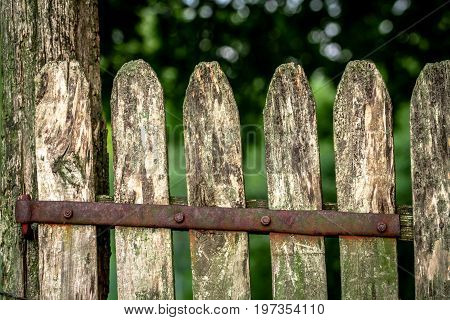 An old wooden fence with a rusted hinge