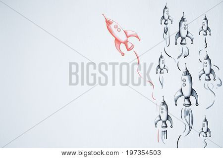 Think differently. Different drawn rocket ship on white wall background. Teamwork concept