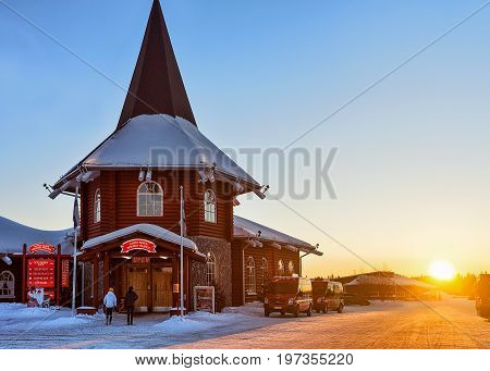 Rovaniemi Finland - March 5 2017: People at Santa Claus Holiday Village with Christmas trees in Lapland Finland Scandinavia on Arctic Circle in winter. At sunset