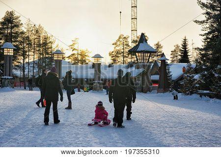People In Santa Village In Lapland Scandinavia At Sunset