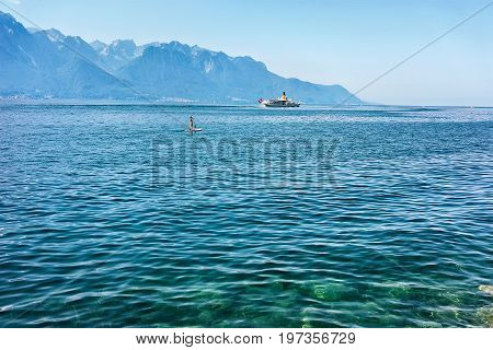 Montreux Switzerland - August 27 2016: Surfer on stand up paddle board and Excursion ship on Geneva Lake of Montreux Swiss Riviera