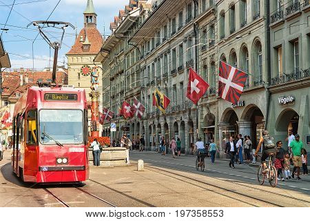 Running Tram And People On Marktgasse Street With Kafigturm Bern