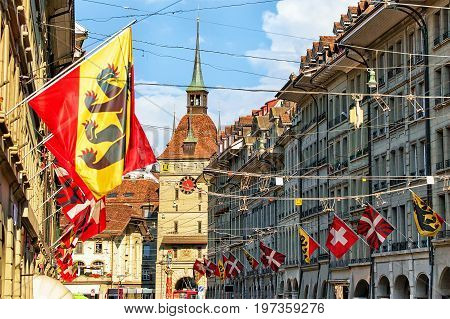 Kramgasse Street With Flags And Roofs And Zytglogge In Bern