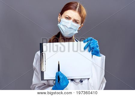Young beautiful woman on a gray background holds documents in a medical dressing gown, medicine, doctor.