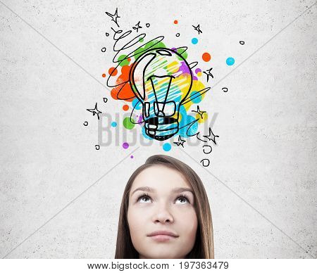 Close up of a head of a dreamy young woman with fair hair looking at a colorful small light bulb drawn on a concrete wall behind her.