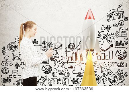 Side view of a blonde businesswoman with a laptop standing near a concrete wall with a rocket and start up icons. Mock up toned image
