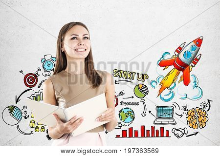 Smiling young woman with a copybook is standing near a concrete wall with a startup rocket and icons. Mock up