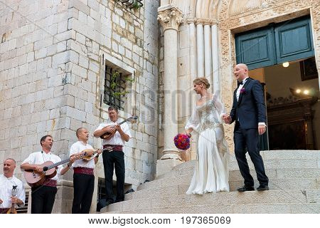 Dubrovnik Croatia - August 20 2016: Musicians singing and playing for Bride and groom at the doorway of the Old church where they are married in the Old city of Dubrovnik Croatia