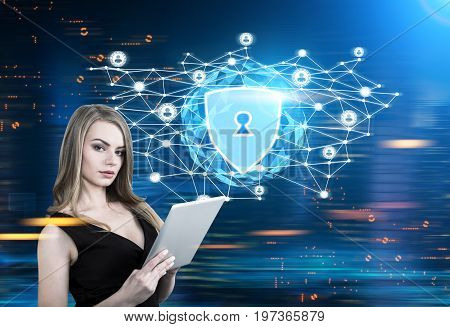 Serious blonde woman in a black dress is holding a tablet computer while standing against a glowing security shield hologram. Blue. Toned image mock up double exposure