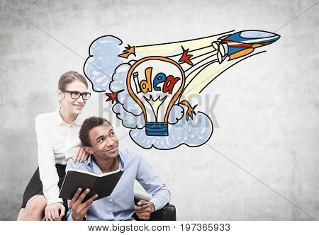African American businessman and his beautiful and smart blonde colleague are sitting in a leather armchair with an open book. Concrete wall background with a colorful startup idea sketch