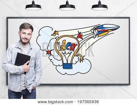 Portrait of a young guy wearing a jeans shirt and holding a book. He is standing near a whiteboard with a colorful startup idea sketch