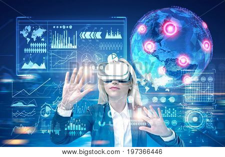 Blonde woman wearing a black suit and VR glasses is interacting with an Earth hologram and infographics in futuristic surrounding. Toned image double exposure.