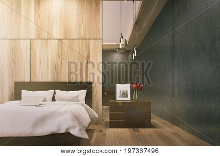 Wooden bedroom interior with a black wall a wooden floor a double bed with a bedside table and a photo on it. 3d rendering mock up toned image