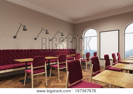 Dark red chairs and sofas are standing near square wooden tables in a coffee shop or a restaurant with a wooden floor beige walls and a vertical poster. Side view. 3d rendering mock up