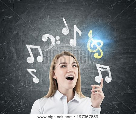 Close up of a young blonde woman composing a tune. She is having an aha moment while standing near a blackboard with music notes drawn on it. Toned image