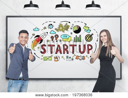 Asian businessman and his blonde colleague wearing an elegant black dress. They are showing thumb up signs and smiling. Whiteboard background startup sketch.