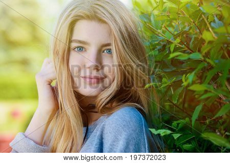 Portrait of a modern teen girl with long blonde hair posing outdoor. Beauty, fashion. Teen style.