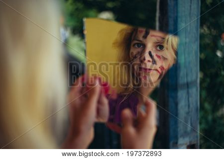 Painted face woman looking at broken mirror