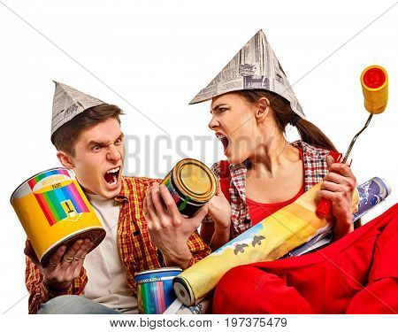 Repair family by happy couple building home. Family renovation in new apartment. Mad woman and man in newspaper cap renovation apartment by painting tools. Quarrels in the family.
