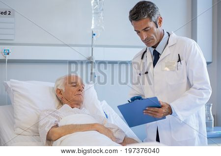 Mature doctor reading medical reports of a senior patient lying on bed at hospital. Doctor on a medical round while checking senior patient report. Professional doctor with clipboard at hospital ward.