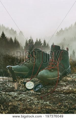Hiking boots with knife and compass on tree log with mountains