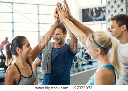 Smiling men and women doing high five in gym. Group of young people making high five gesture in gym after workout. Happy successful fitness class after training.