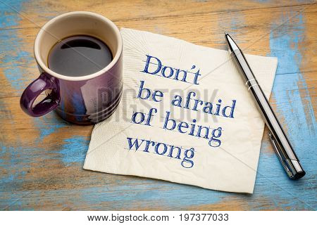 Do not be afraid of being wrong - inspirational handwriting on a napkin with a cup of espresso coffee