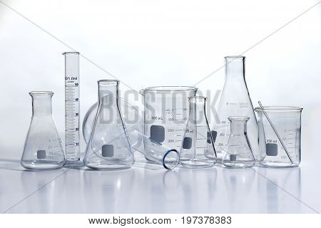 Laboratory glassware on white reflective table