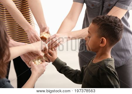 Cute little boy taking piece of bread from hand. Poverty concept