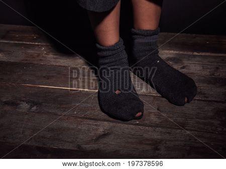 Feet of little boy in leaky socks. Poverty concept