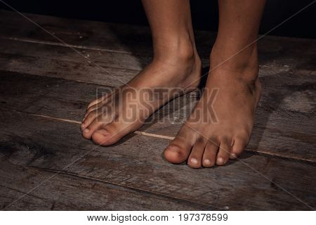Dirty feet of little boy. Poverty concept
