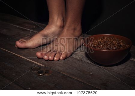 Dirty feet of little, bowl with lentils and coins on floor. Poverty concept