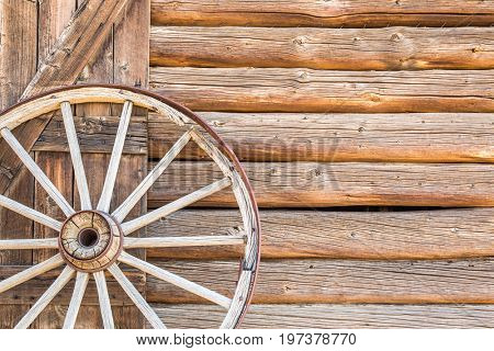 Abstract of Vintage Antique Log Cabin Wall and Wagon Wheel.