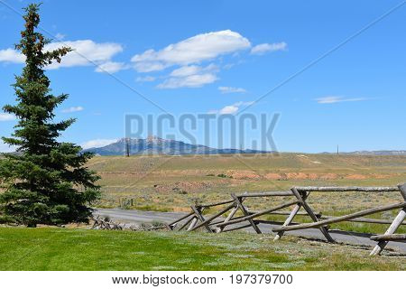 Cody Wyoming Landscape with rail fence, prairie, trees and distant mountains,
