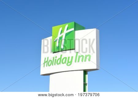 CODY, WYOMING - JUNE 24, 2017:  Holiday Inn Sign against a blue sky. The American hotel chain is owned by InterContinental Hotels Group.